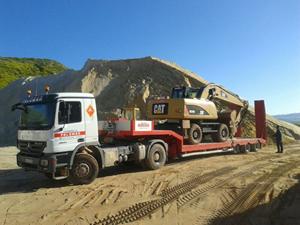 camión transportando excavadora