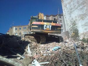 excavadora junto a escombros